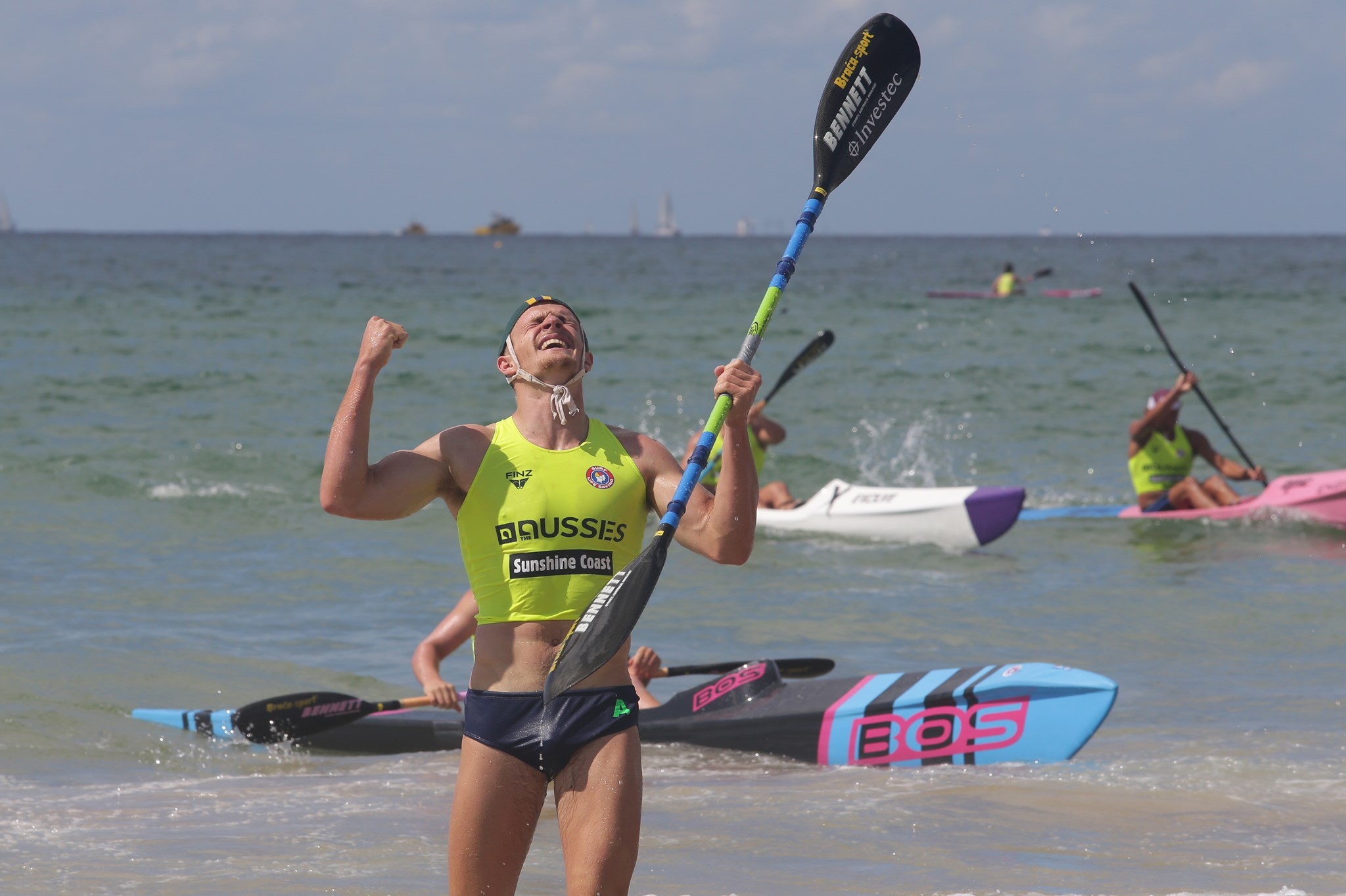 Fletcher Armstrong celebrates win on beach with ski paddle in hand